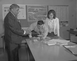 B.C. Vocational School; BTSD Basic Training program instructor with two students and a microscope...