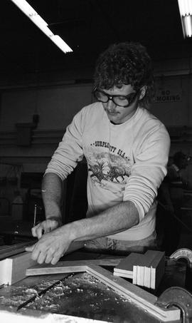 BCIT Carpentry, 1989, man wearing eye protection cutting wood [3 of 7 photographs]