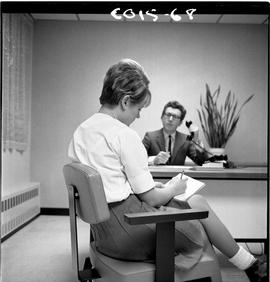 B.C. Vocational School; Commercial Program instructor sitting at a desk and a student sitting on ...