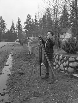 Survey, 1964; two men using surveying equipment in a residential area [2 of 2]