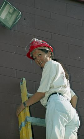 Pre-trade Aboriginal women; student wearing a hard hat at the top of a ladder