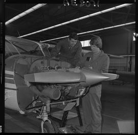 BC Vocational School; Aeronautics students working on a small propeller aircraft engine inside th...