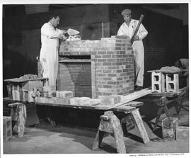 Bricklaying; two students building a brick fireplace ; Photo by the Division of Visual Education,...