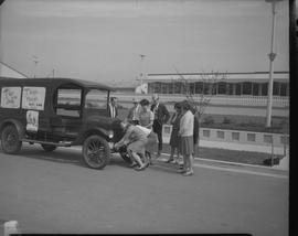 "Group of students (?) standing near an automobile with posters that read """"T""-off ..."