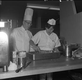 BC Vocational School Cook Training Course ; instructor supervising as student stirs food in a pan