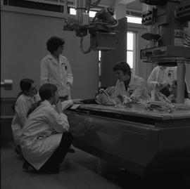 Medical radiography, 1968; six people examining a skeleton on an x-ray table