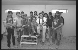 Students holding power tools and posing for a group shot during gym construction [1 of 8 photogra...