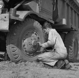 Logging, 1969; a man using a wrench to remove lug nuts from a hub cap on a dump truck