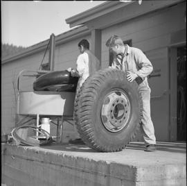 Logging, 1968; a man holding a large tire ; man working in background