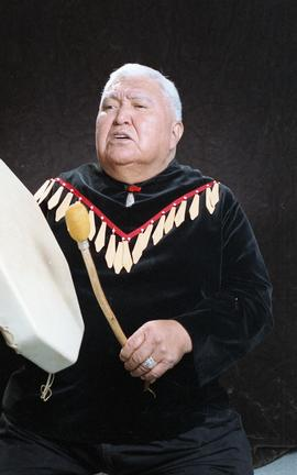 Bob George, First Nations elder, in First Nations garment playing an instrument [28 of 36 photogr...