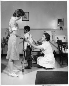 Nurse and BCVS Practical Nursing student helping child with crutches (ca. 1963)