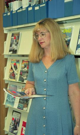 Woman next to magazine rack, Lori Pederson, original Aerospace Technology Campus (ATC) Library [3...