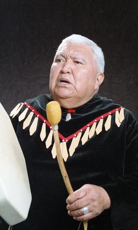 Bob George, First Nations elder, in First Nations garment playing an instrument [21 of 36 photogr...