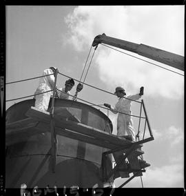 B.C. Vocational School image of Boilermaker students standing on scaffolding and guiding part of ...