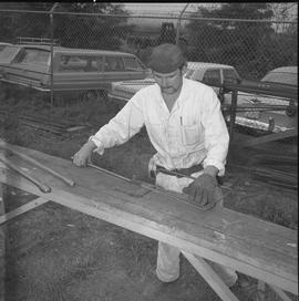 Structural steel, 1971; man shaping a piece of steel cable