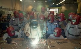 BCIT women in trades; welding, female students in welding shop wearing helmets and watching instr...