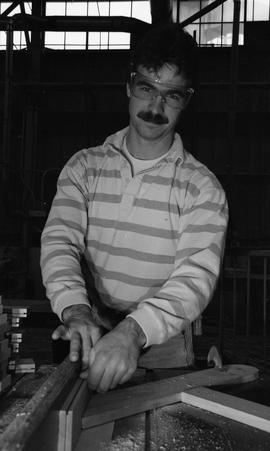 BCIT Carpentry, 1989, man wearing eye protection cutting wood [4 of 7 photographs]