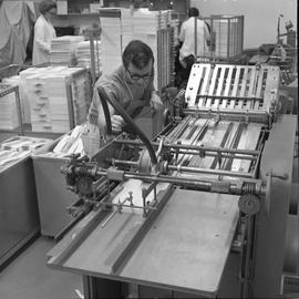 BCVS Graphic arts ; a man watching a paper folding machine ; stacks of paper in background [2 of 3]