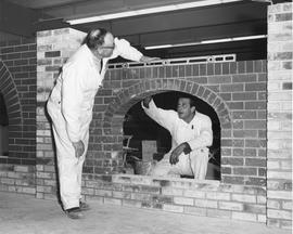 Bricklaying; two men building the arch and mantel of a fireplace in a workshop