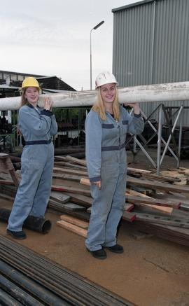 BCIT women in trades; plumbing, students in uniforms and hard hats carrying piping material [7 of...