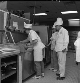BC Vocational School Cook Training Course ; student rolling out pie crust ; instructor (Arthur L....
