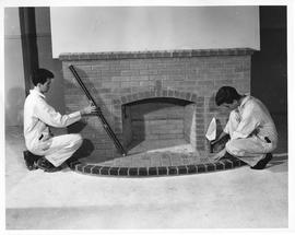 Bricklaying; two students building a brick fireplace - one student tapping a brick in the hearth ...