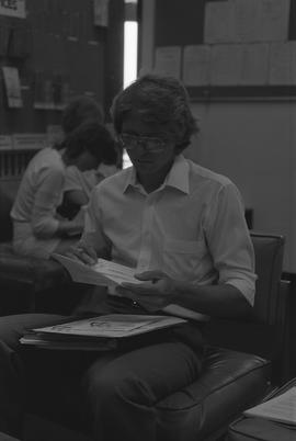 Man sitting down and looking at a piece of paper; two students sitting in background