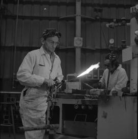 Welding, 1968; man turning on a welding torch ; man working in background