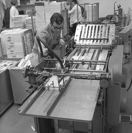 BCVS Graphic arts ; a man watching a paper folding machine ; stacks of paper in background [1 of 3]