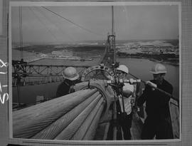 Structural steel; three men working a steel cable for the suspension of A. Murray Mackay bridge c...