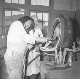 Tire repair, Nanaimo, 1967; instructor watching a student that is repairing the inside of a tire