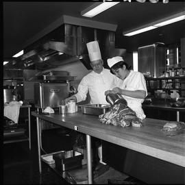 BC Vocational School Cook Training Course ; instructor supervising as student pours food into a pan