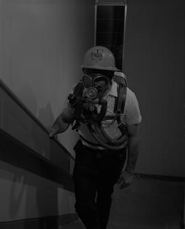 Mining, 1966; a man walking up stairs wearing a gas mask and hard hat