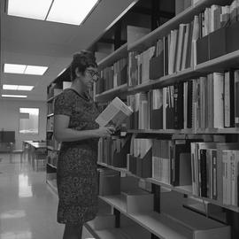 BCIT Burnaby campus library ; a woman standing in an aisle reading a book
