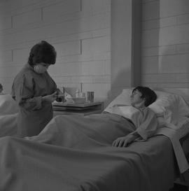 Practical nursing, Prince George, 1968; a nurse preparing bandages for a patient lying on a hospi...