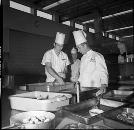 BC Vocational School Cook Training Course ; student puts seasoning on food while the instructor, ...