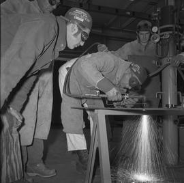 Welding, Terrace, 1968; three men watching another man welding a sheet of metal