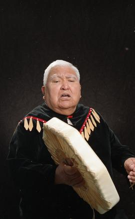 Bob George, First Nations elder, in First Nations garment playing an instrument [14 of 36 photogr...