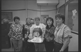 Staff posing with pumpkin carving of a crying baby [2 of 2 photographs]