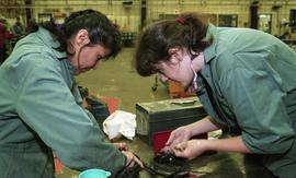 BCIT women in trades; heavy duty, students in uniforms using mechanical tools and equipment [3 of...