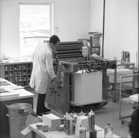 BCVS Graphic arts ; a man adjusting printing equipment ; ink and paper on tables in foreground