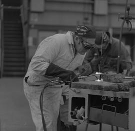 Welding, 1968; man wearing protective goggles and gloves welding ; man working in background [2 o...