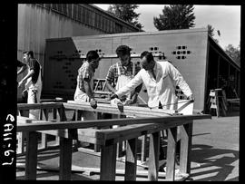 B.C. Vocational School image of a Carpentry Trades instructor teaching students in the yard outsi...