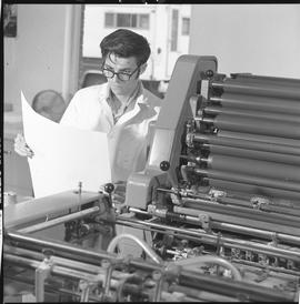 BCVS Graphic arts ; man standing next to a printing press and looking at a poster