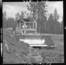 Heavy duty equipment operator, Nanaimo ; man operating a bulldozer ; forest in background
