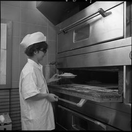 BC Vocational School Cook Training Course ; student putting a pie into an oven