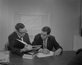Business Management; two men sitting at a desk looking at a merchandising textbook