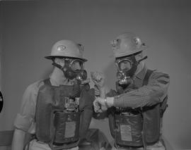 Mining, 1966; two men wearing gas masks and hard hats, one man checking another man's pulse
