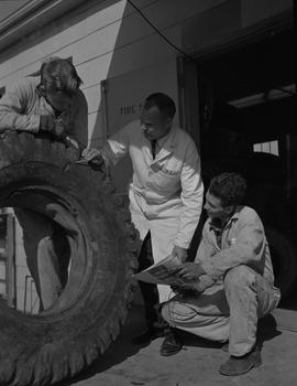 Tire repair, Nanaimo, 1967; instructor and two students examining a gouge in a tire