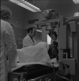 Medical radiography, 1968; four people examining a manikin on an x-ray table